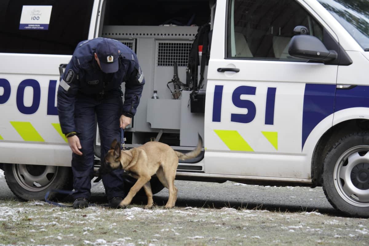 Poliisi ja koira poliisin partioauton edessä