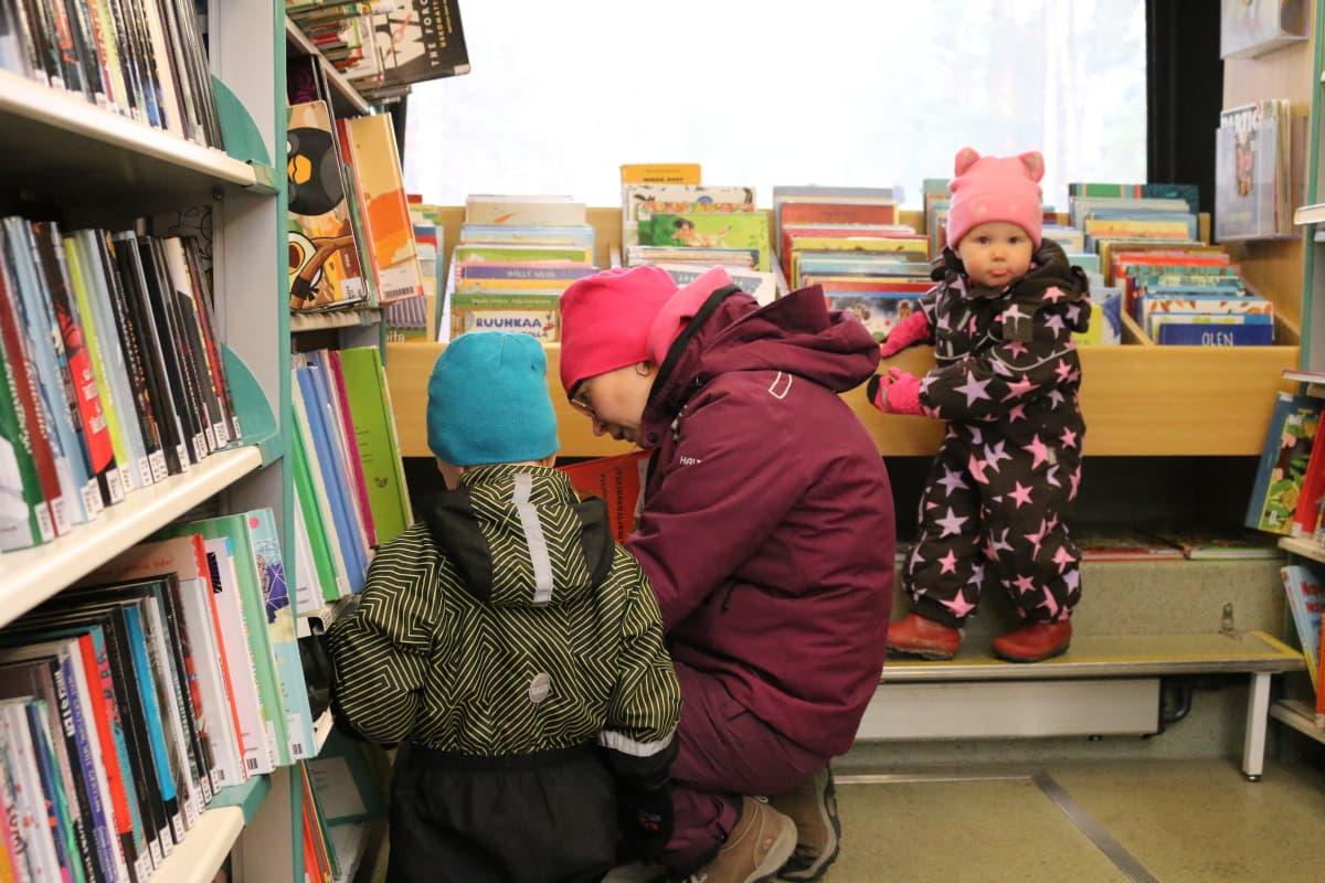 äiti ja kaksi lasta kirjastoauton asiakkaina