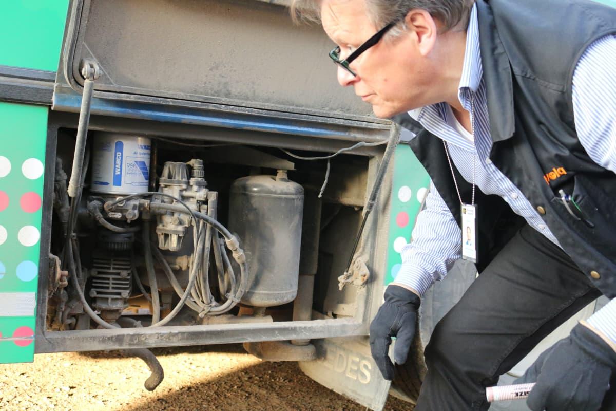 kirjastoauton kuljettaja katselee auton tekniseen tilaan