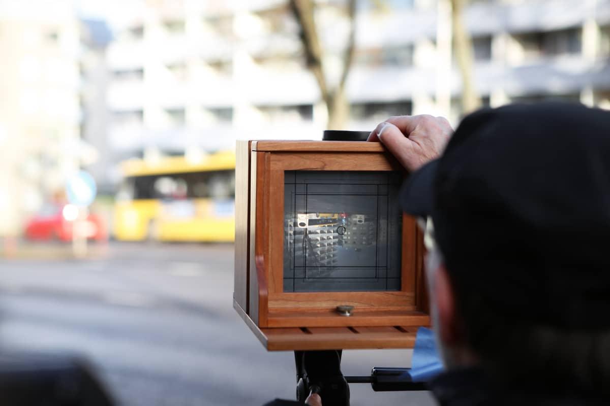 Mies ottaa valokuvan 1840-luvun malliin rakennetulla kameralla.