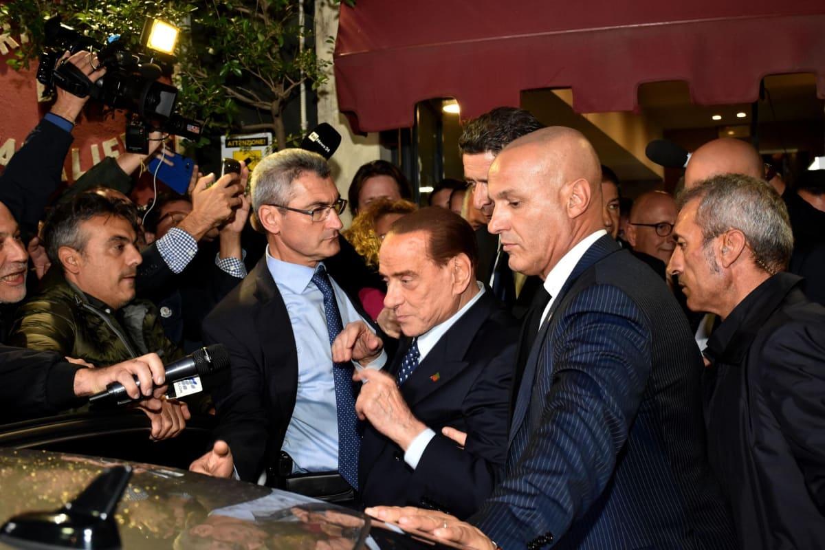 Silvio Berlusconi ja muita mieshenkilöitä toimittajien edessä.