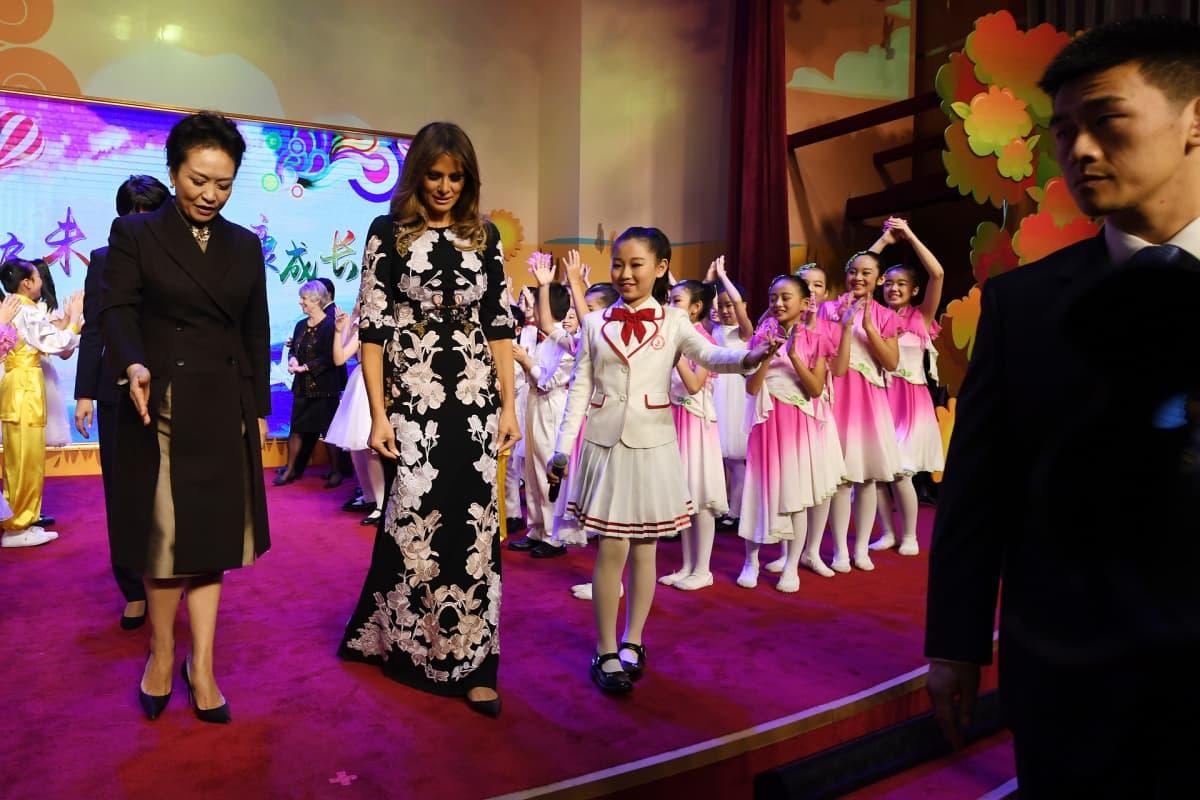 Peng Liyuan ja Melania Trump koululaisten saattelemina.