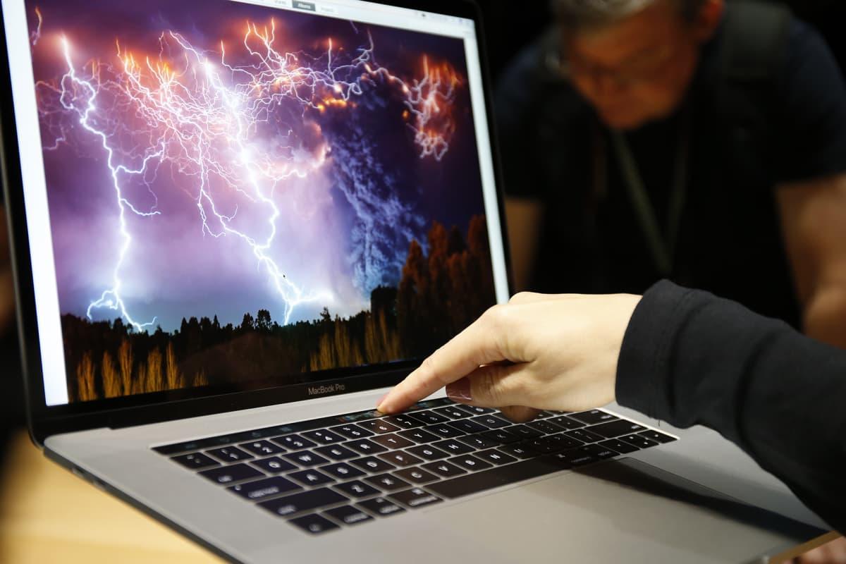 Naisen käsi Apple kannettavan tietokoneen näppäimistöllä.
