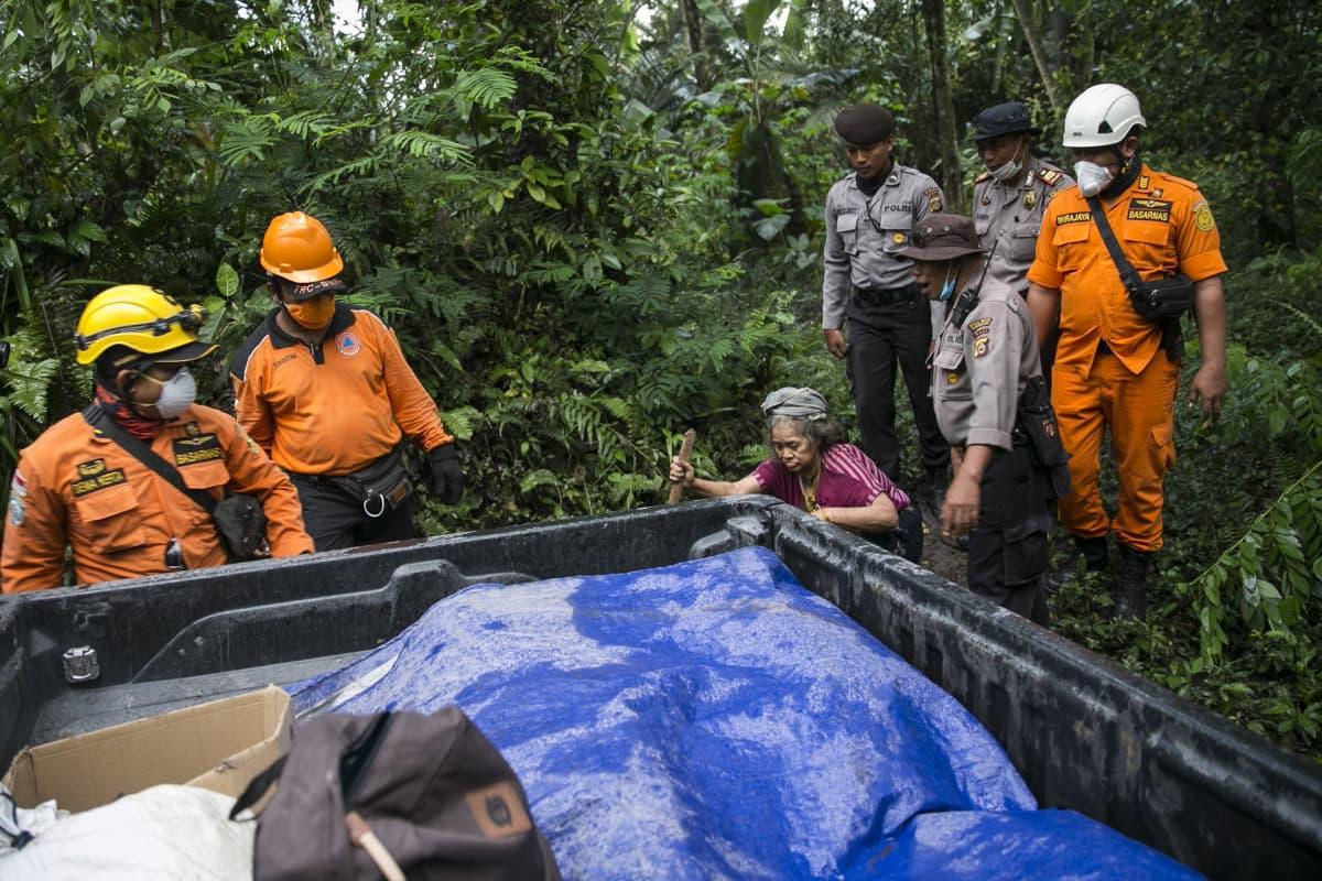Indonesian viranomaiset evakuoimassa paikallista naista