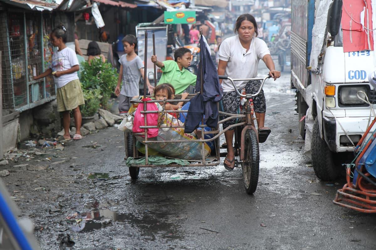 Äiti vie lapsia pyörävaunilla.