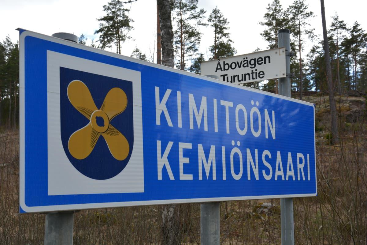 Vägskylt med texten Kimitoön Kemiönsaari samt Kimitoöns kommunvapen.