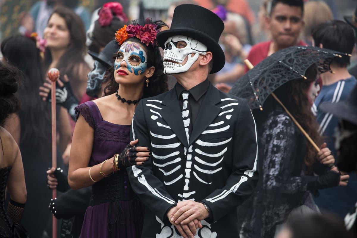 James Bond ja nainen naamioituneena kulkueessa.