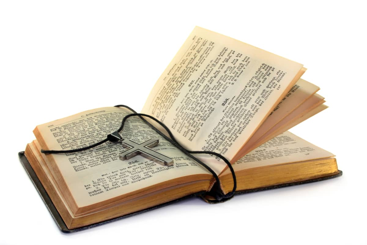 Ristinmallinen kaulariipus avoimen Raamatun päällä