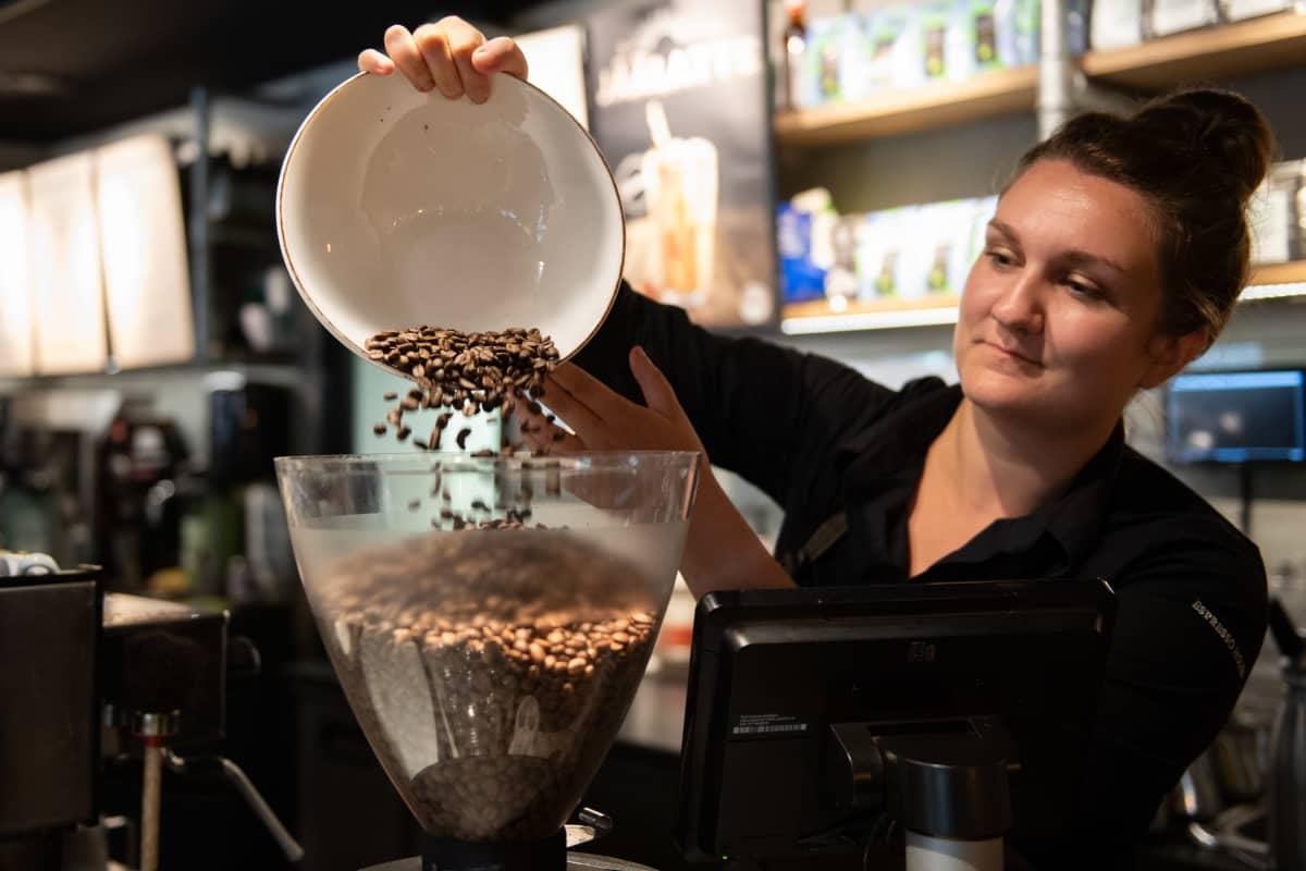 kahvilan työntekijä kaataa papuja espressokoneeseen.