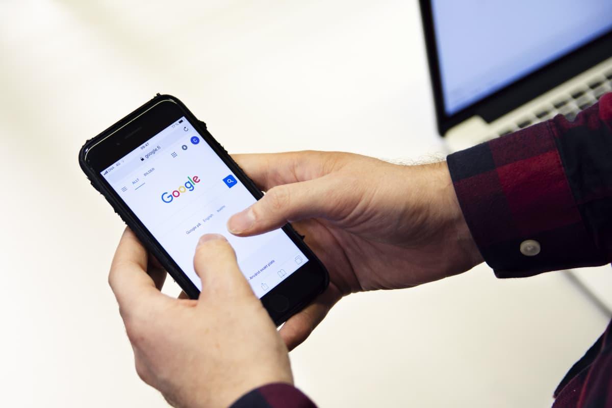 Henkilö puhelimella Googlen haussa.