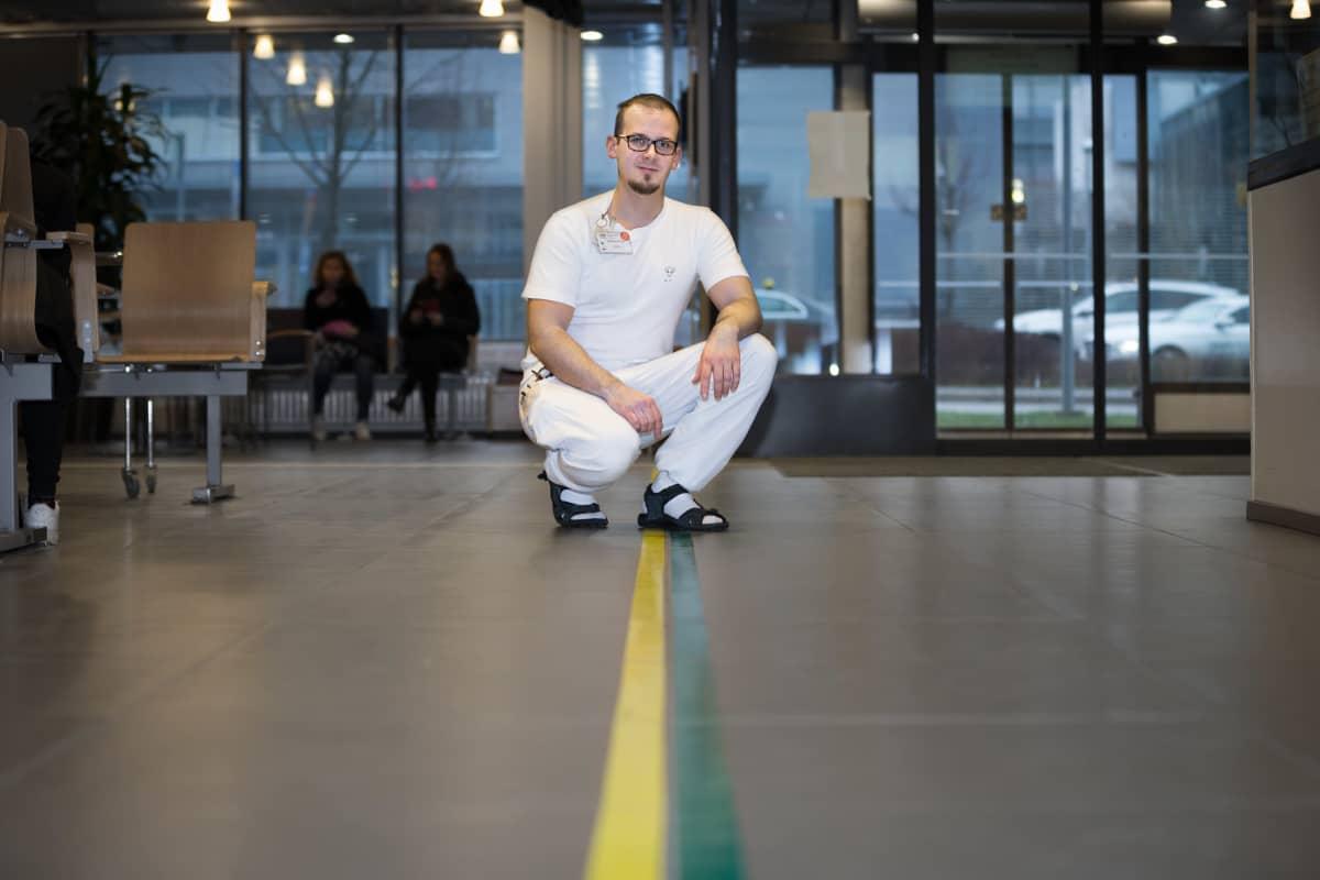 Jesperi Kuorikoski kyykyssä lattialla sairaalan aulassa.