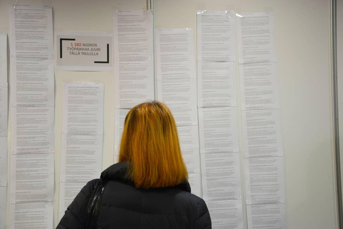 Nainen lukee työpaikkailmoituksia.
