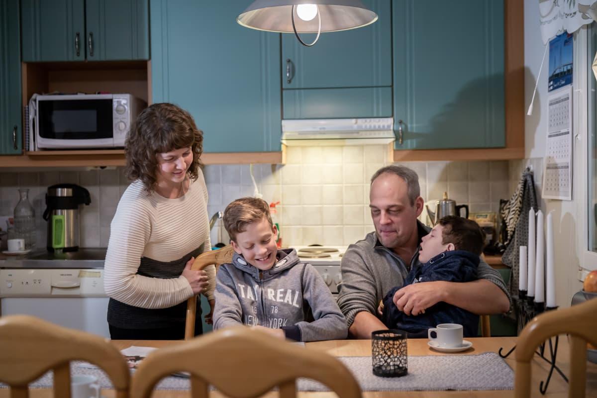 Eklundin perhe keittiössä, äiti Viveka (vas), läksyjä tekevä Verner, isä Mika, ja sairas poika Ludvig sylissä. 3.12.2018.