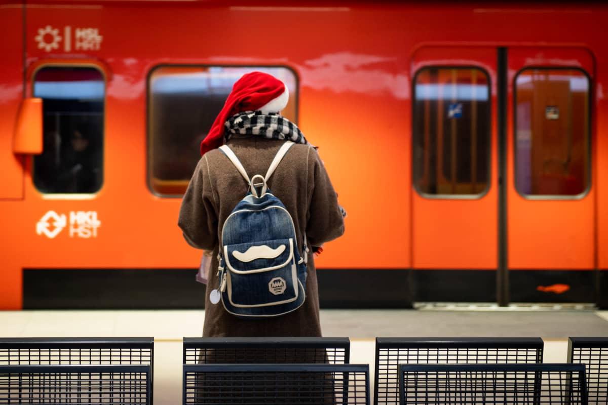 Nainen tonttulakki päässään odottaa metroa.