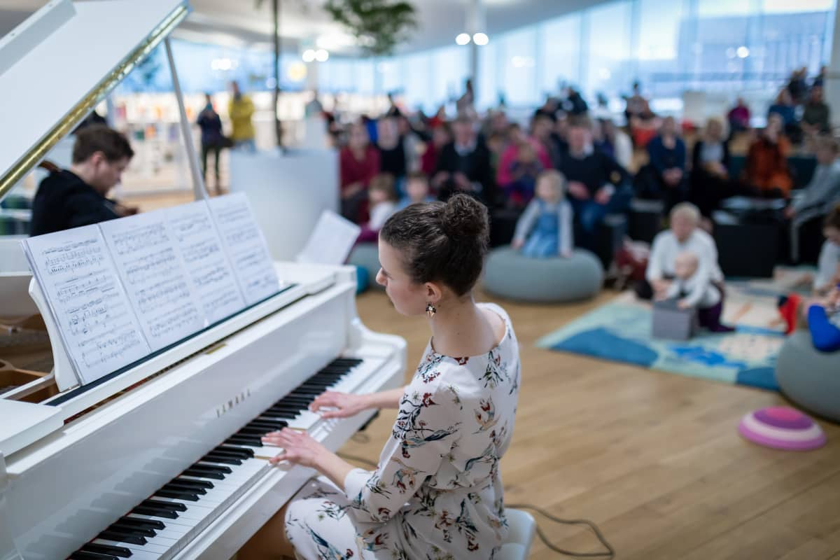 Sellisti Jussi Makkonen (vas) ja pianisti Nazig Azezian (etualalla) soittamassa lapsiperheyleisölle, Keskustakirjasto Oodi, 28.2.2019.