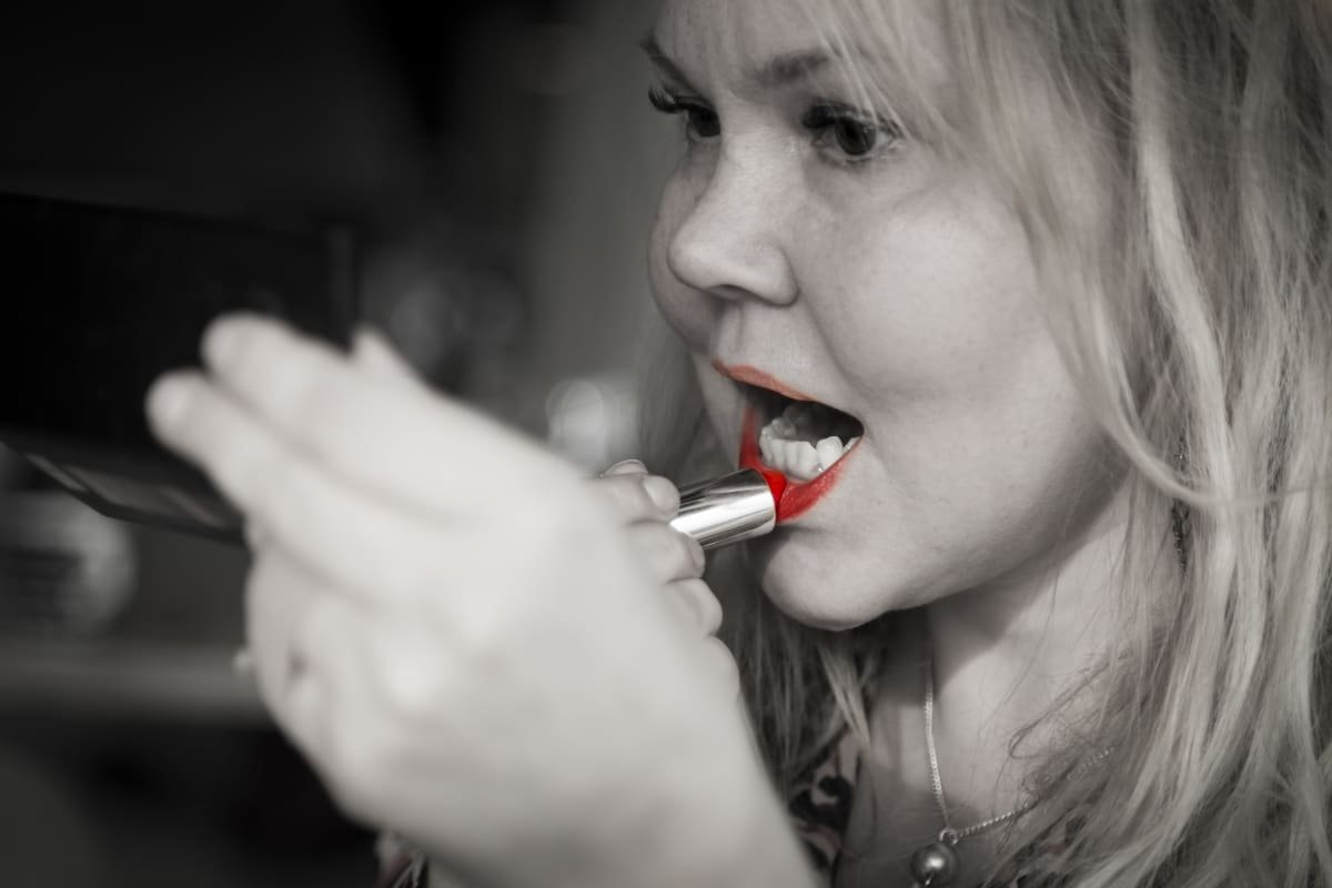 Katja Kettu laittaa huulipunaa.