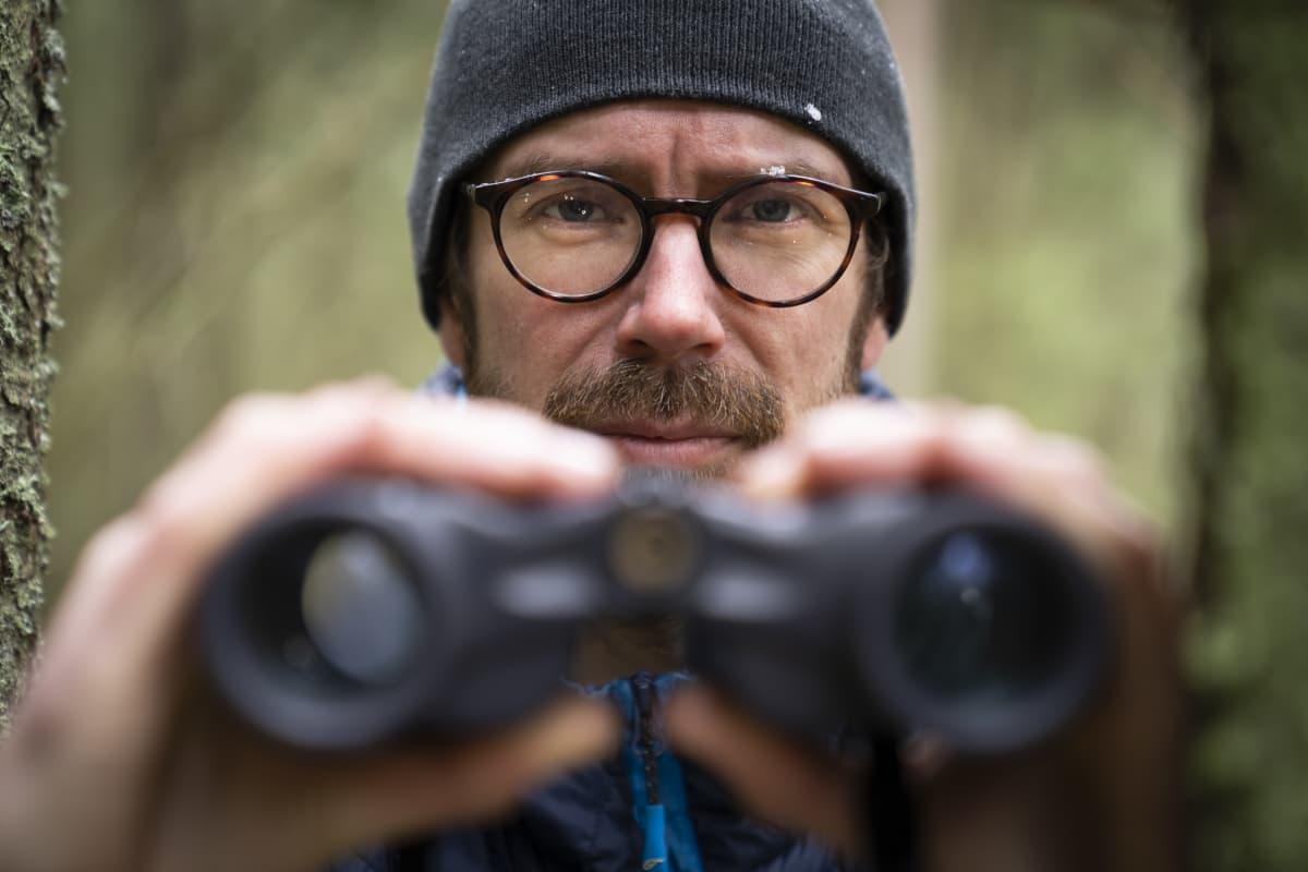 Juha Kauppinen katsoo kiikareilla metsässä.