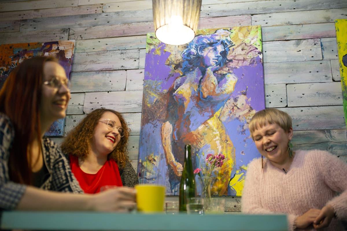 Jemina Viitala (vas), Mertta Hätinen ja Laura Liimatainen Helsingin Lauttasaaressa sijaitsevassa Maker´s -kahvilassa. Taustalla Simon Arnsin tekemä Havis Amanda -maalaus.