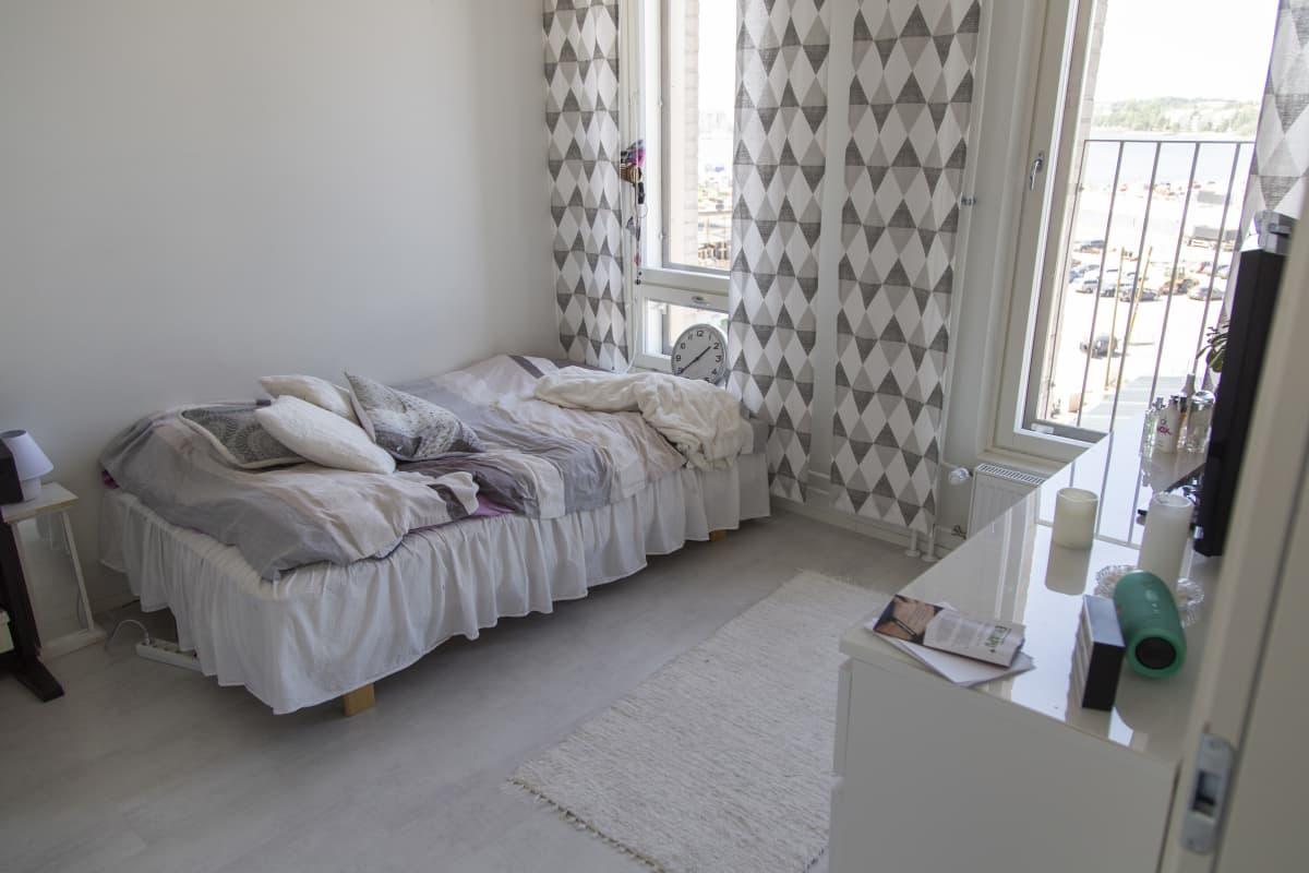 Opiskelija-asunnossa sänky ja muita tavaroita.