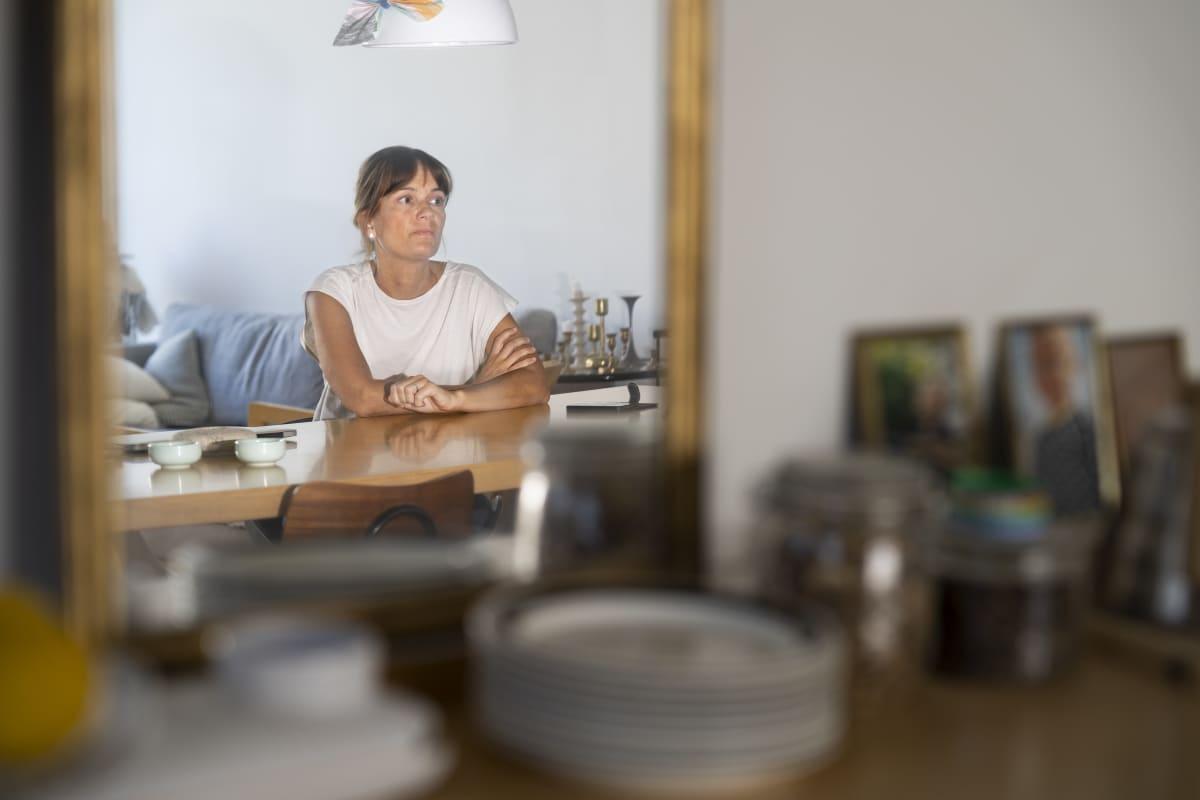 Jenni Anttila pöydän äärellä peilin kautta nähtynä.