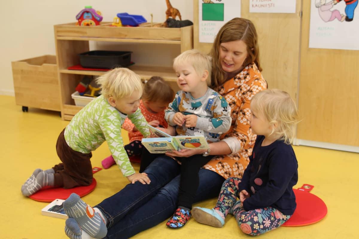 Lastentarhanopettaja lukee lapsille kirjaa.