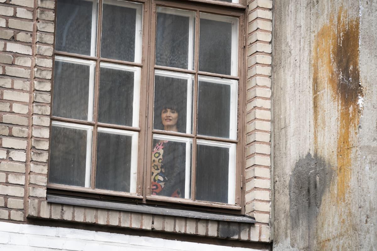Maija Vilkkumaa ikkunassa.
