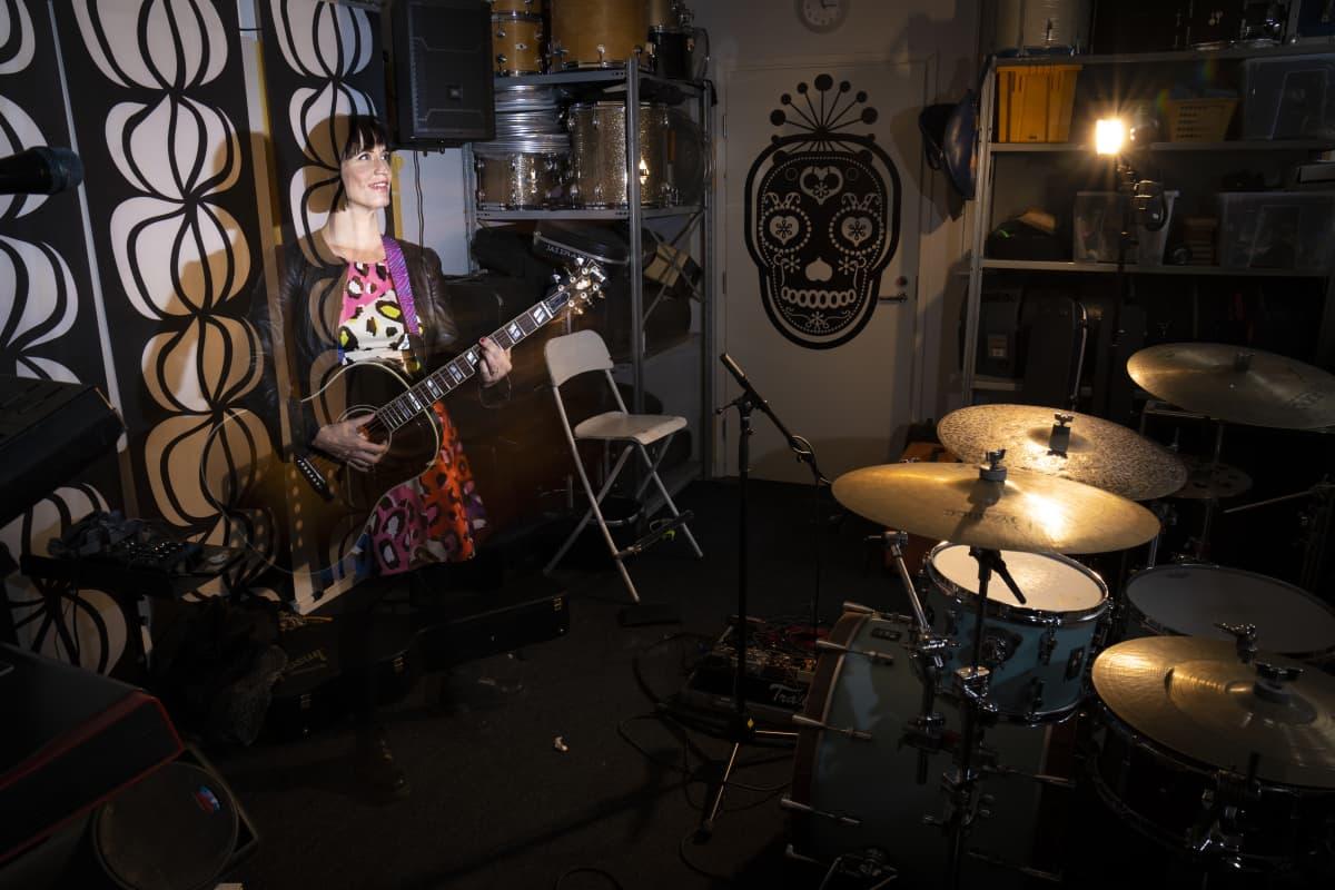 Maija Vilkkumaa soittaa kitaraa treenikämpällä.