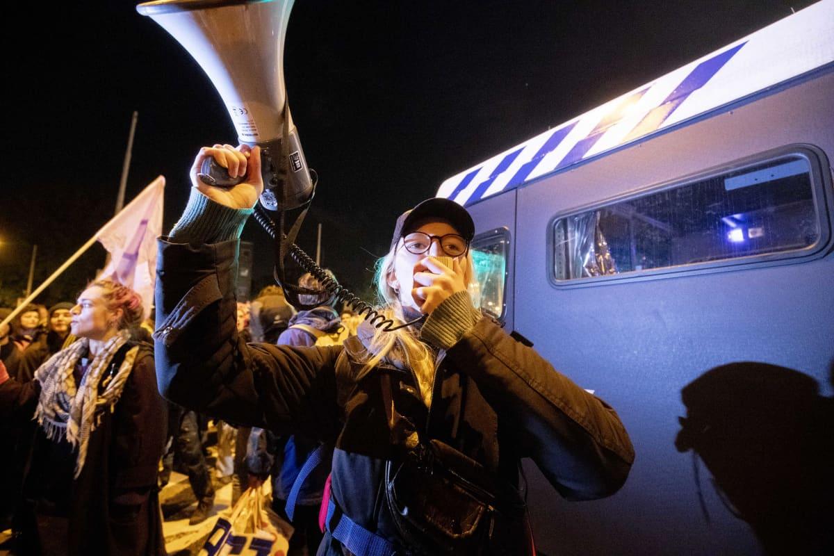 Kuvassa mies huutaa megafoniin Amsterdamissa.