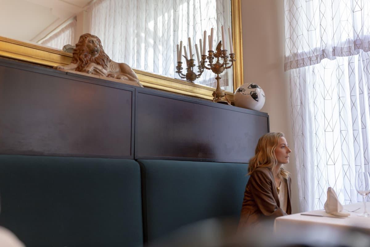 Mariska istuu ravintola Kosmoksen pöydässä.