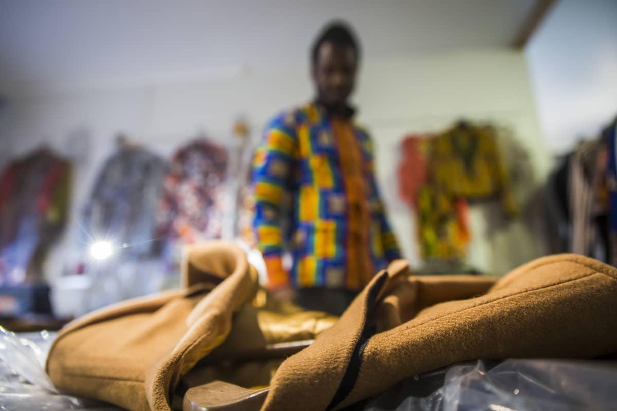 Dennis Owusu seisoo pöydän takana ja pöydällä on hänen suunnittelemansa takki