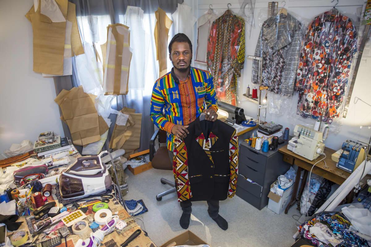Dennis Owusu seisoo työhuoneessaan ja pitää suunnittelemaansa paitaa kädessä