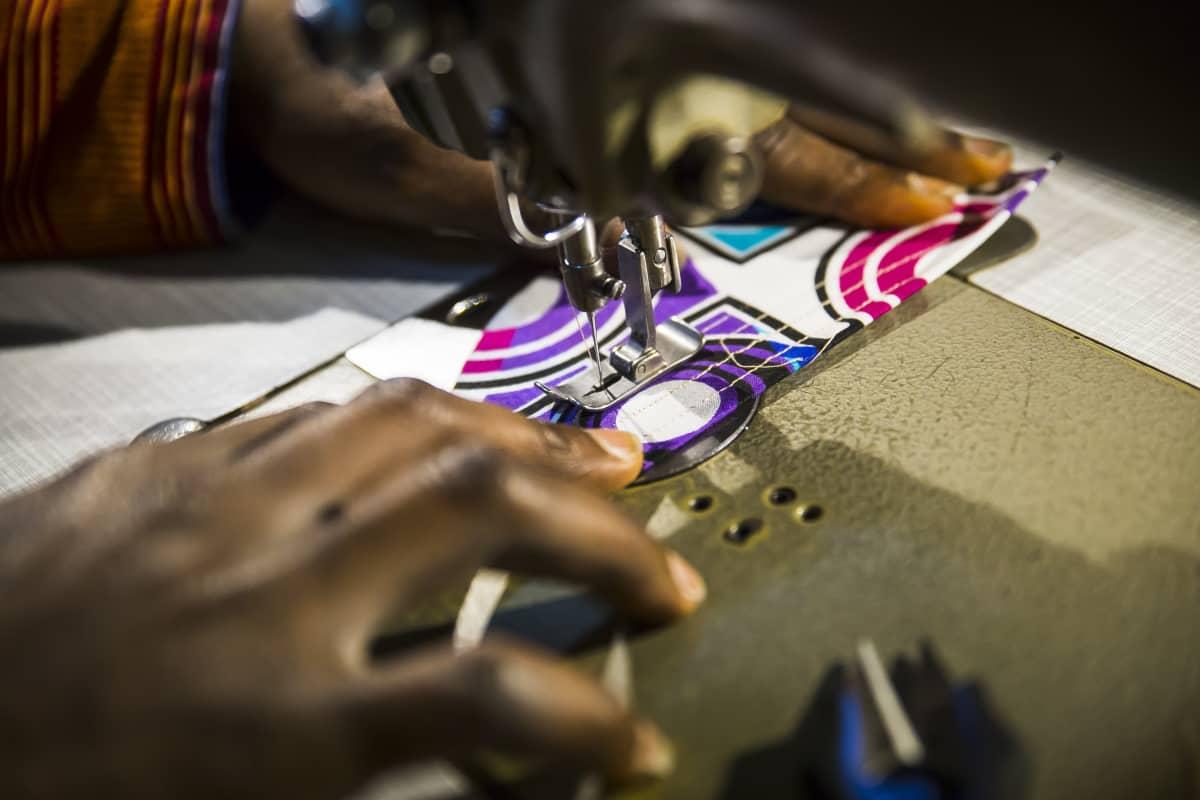Dennis Owusu ompelee ompelukoneella