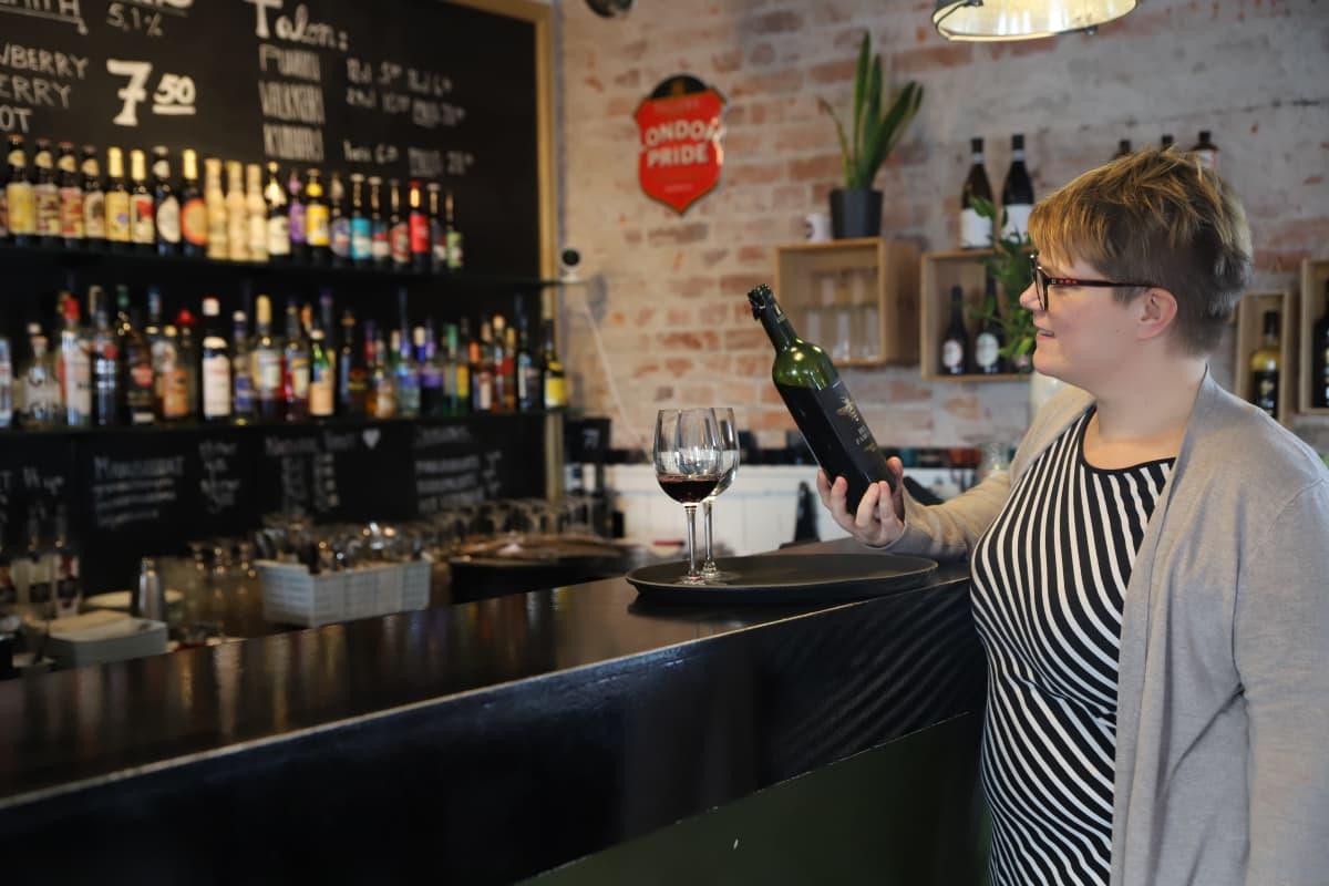 Maija Munkki kaataa viiniä lasiin.