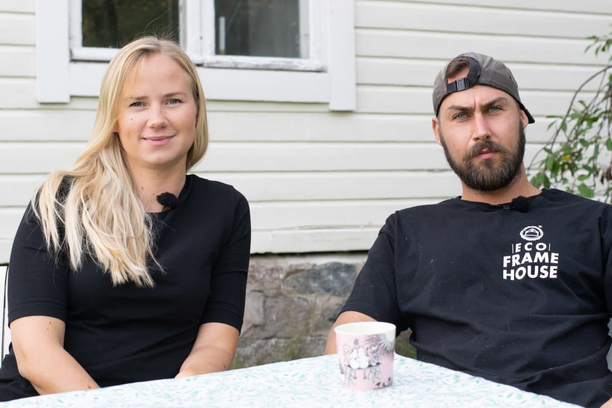 Ett ca 30-årigt par, en man och en kvinna, sitter utomhus vid ett trädgårdbord. De ser mot kameran. I bakgrunden ett vitt trähus.