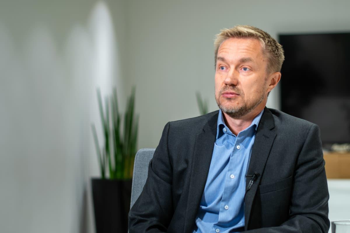 Direktör iklädd kavaj och kragskjorta sitter i ett mötesrum och blir intervjuad.