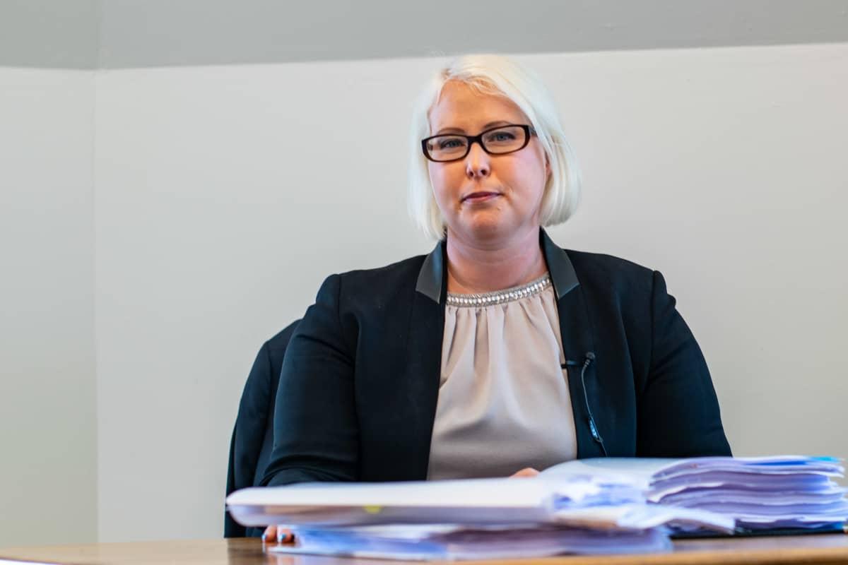 Porträttbild av kvinnlig advokat med blont hår och glasögon med mörka bågar.