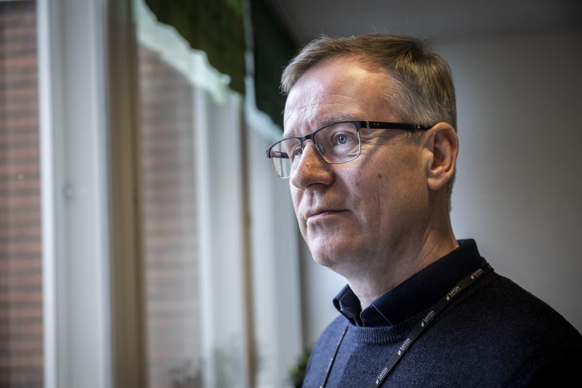 kuntayhtymän johtaja Heikki Helve presidentinkadun oppilaitoksen aulassa katsomassa ikkunasta ulos