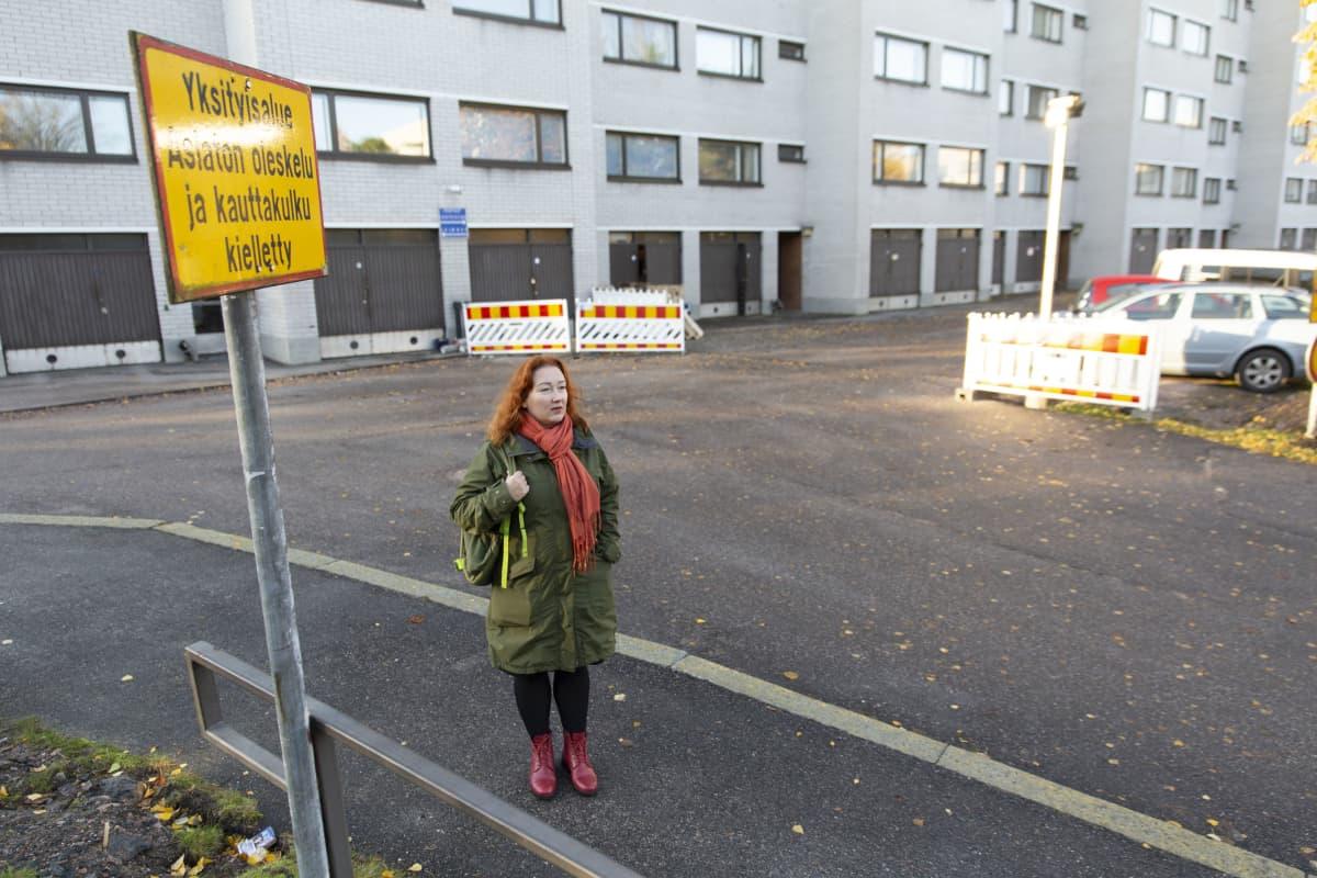 Nina Kuujärvi seisoo pihalla. Taustalla taloyhtiö, jonka kellariin lukkojen taakse hänen postipakettinsa toimitettiin. Kyltti: Yksityisalue - asiaton oleskelu ja kauttakulku kielletty.