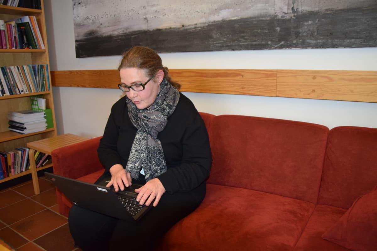 Nainen istuu sohvalla ja näpyttelee tietokonetta.