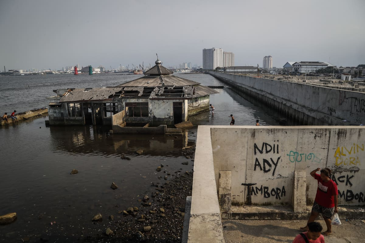 Jakartan suojaksi merenpinnan nousulta on rakennettu muuri. Muurin edustalla näkyy meren rikki huuhtoma talo.
