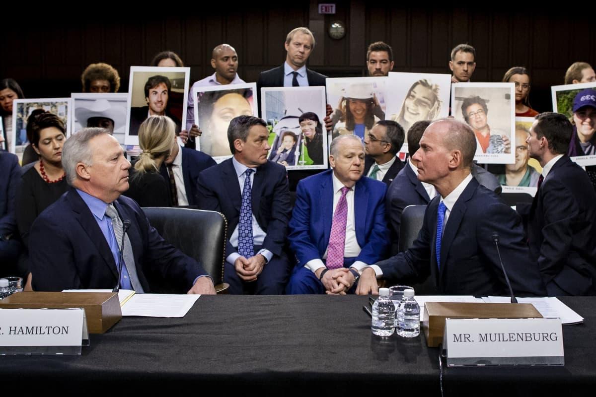 Boeingin toimistujohtaja Dennis Muilenburg ja muita yhtiön johtohahmoja senaatin kuulemistilaisuudessa. Taustalla omaiset pitävät esillä kuvia lentoturmissa menettämistään perheenjäsenistään.