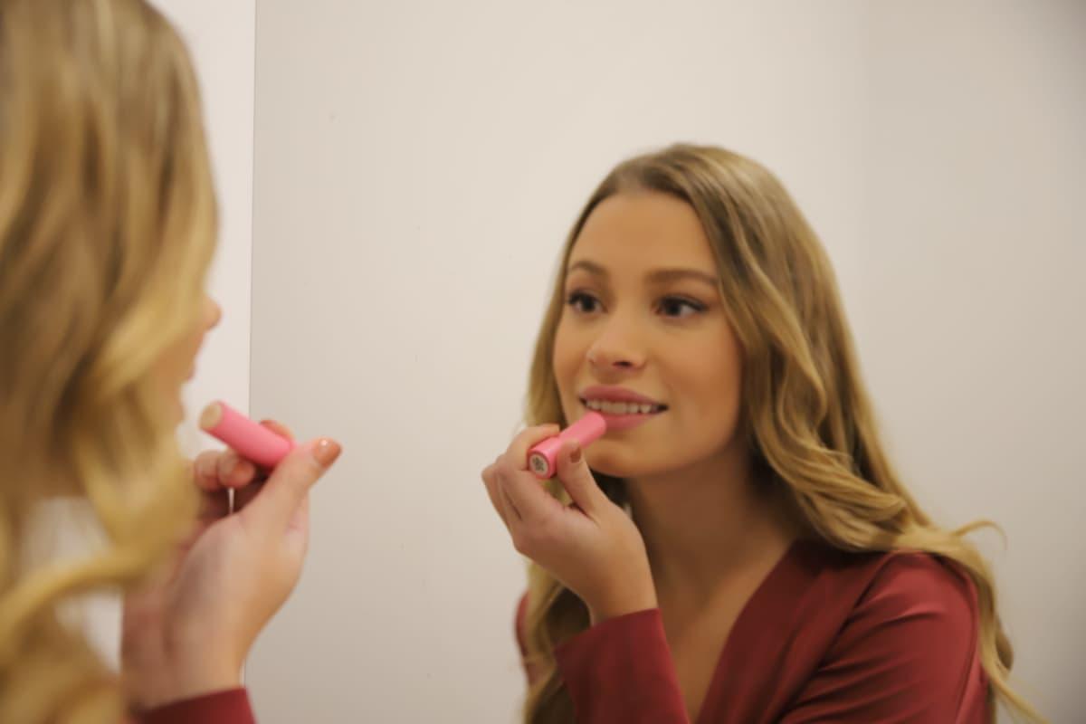 Nuori nainen laittaa huulipunaa peilin edessä