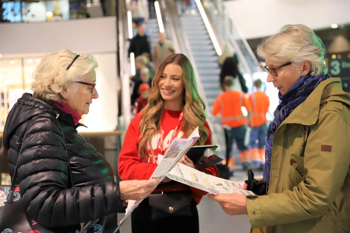 Nuori nainen opastaa kahta vanhempaa rouvaa ostoskeskuksen käytävällä