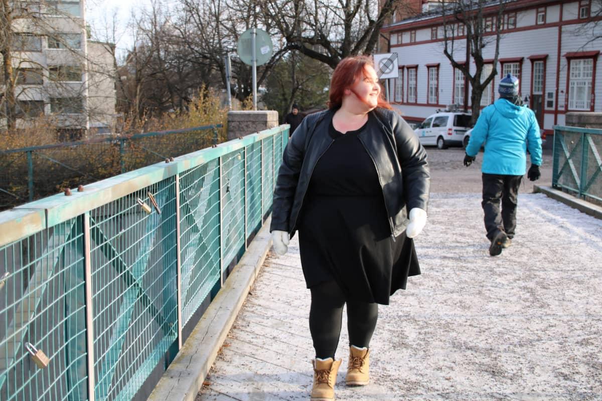 Nainen kävelee hymyillen sillalla