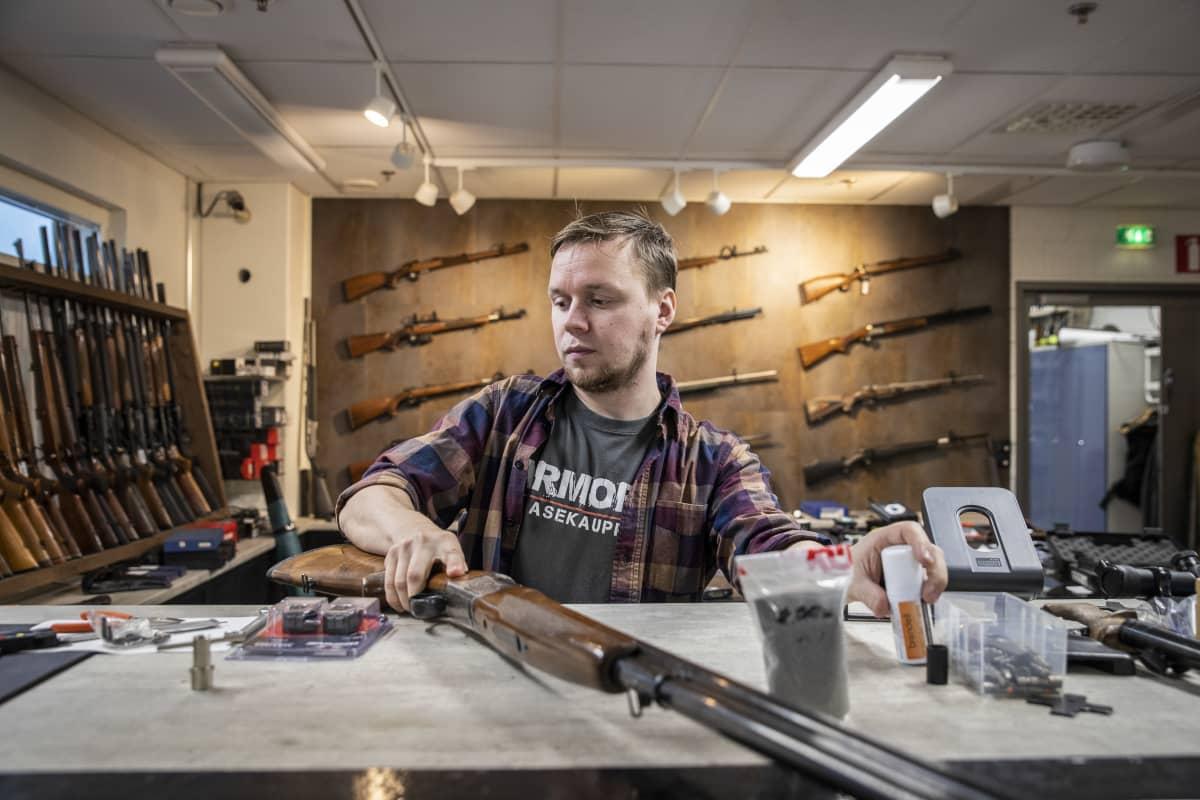 Armoria ase-liikkeen yrittäjä Veli-Matti Iskanius käsittelee haulikkoa liikkeen pöydällä.