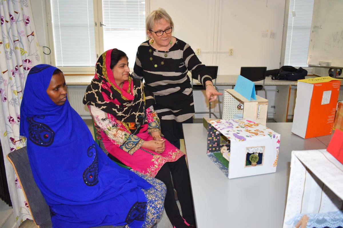 Opettaja Riitta Malila katselee nukkekoteja opiskelijoiden kanssa.