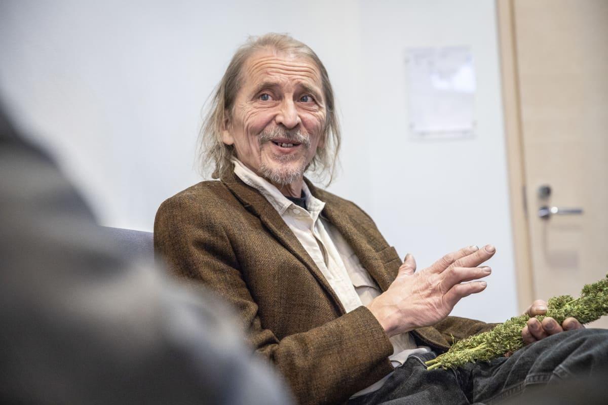 Hannu Hyvönen pitää kannabiskasvia kädessään käräjäoikeusistunnossa.