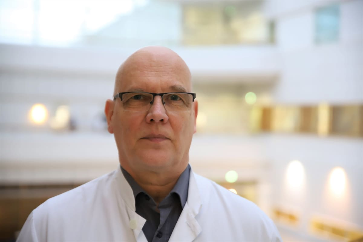 Ylilääkäri Esa Rintala seisoo Turun yliopistollisen keskussairaalan aulassa.