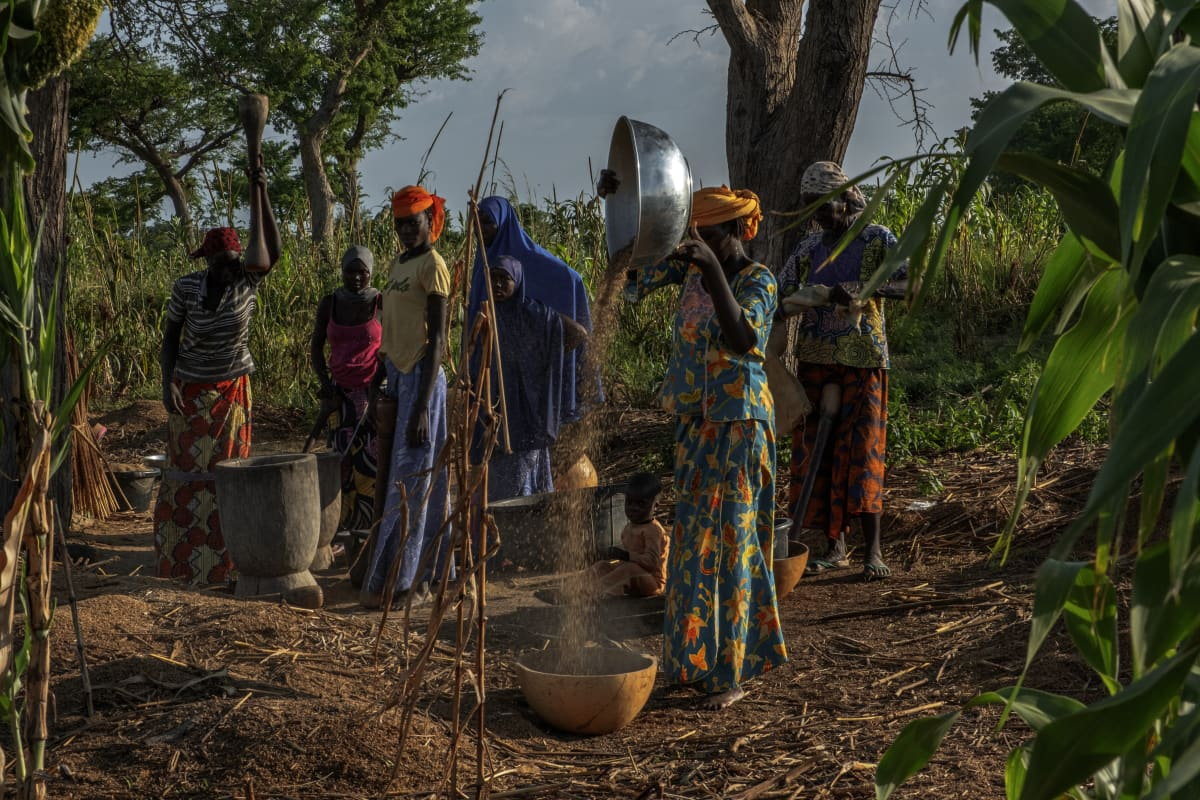 Naisia kaatamassa hirssiä kulhosta, muita taustalla.