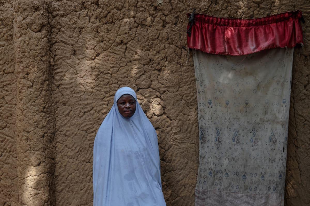 Nainen savitiilestä rakennetun talon edessä.